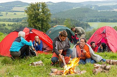 Sitting by campfire friends in tents chatting